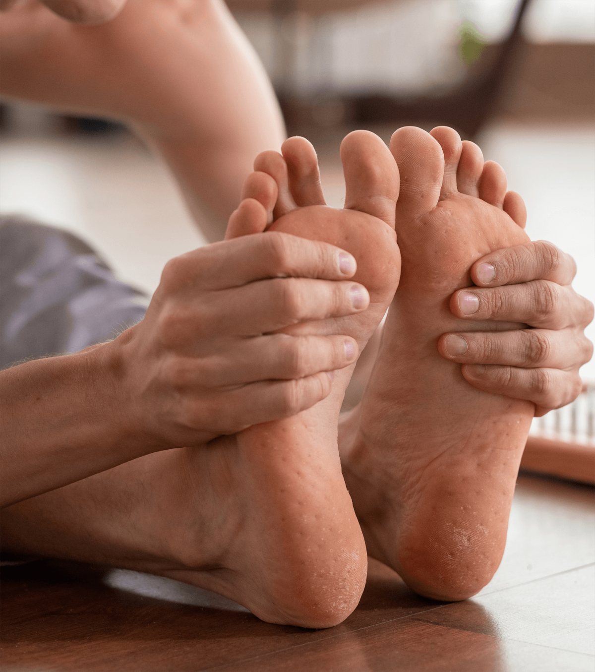 barefoot-man-sitting-on-wooden-floor-and-holding-h-BMLN7DQ-1200x1355.png